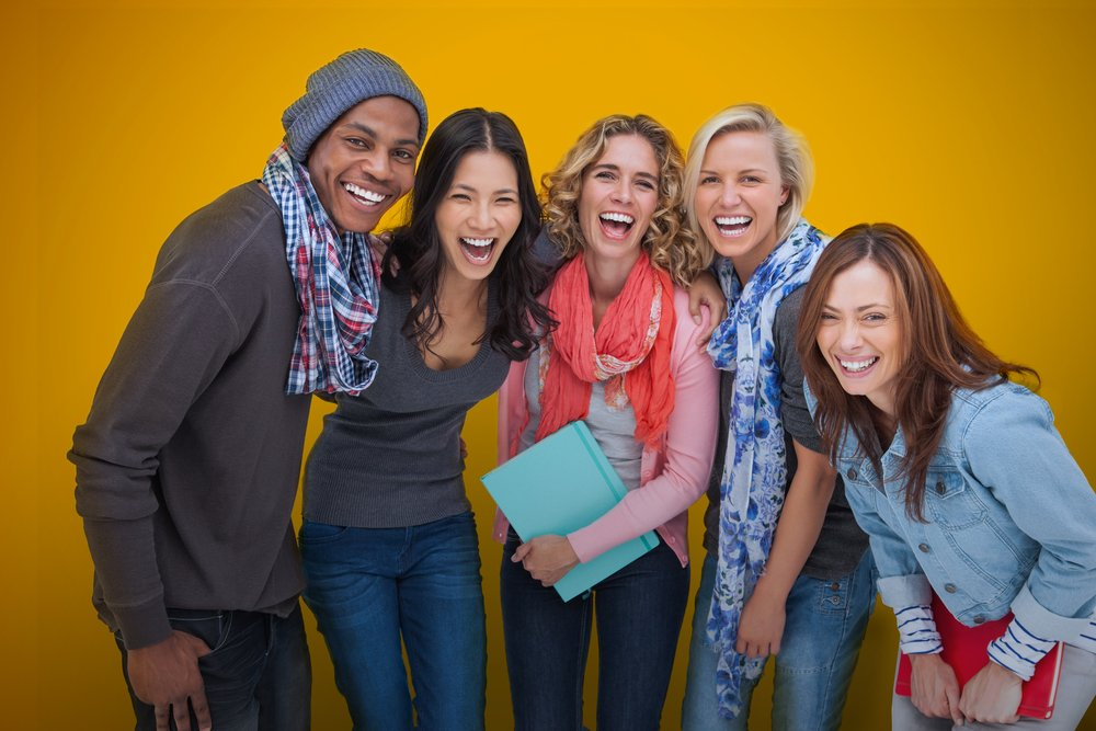 Cheerful group of friends laughing together on yellow background